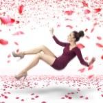 aantrekkelijke dame vallen over rozenblaadjes achtergrond — Stockfoto