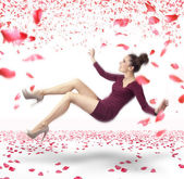 Attractive lady falling down over rose petals background — Stok fotoğraf