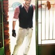 Fashion style man in the old wicket gate — Stock Photo