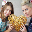 Mother and daughter keeping toy heart - Stok fotoğraf