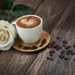 Hot coffee and beautiful white rose - Stock Photo