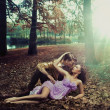 A loving couple lying on autumn leaves — Stock fotografie