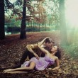 A loving couple lying on autumn leaves — Stock Photo