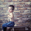 Small kid playing on the suitcase — Stock Photo