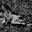 Couple lying on autumn leaves — Foto de stock #19358897
