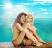Two half-naked female friends over the colorful background — Stock Photo