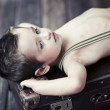 Child boy relaxing on the suitcase - Stockfoto
