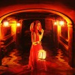 Stock Photo: Romantic lady in red holding lantern in dark dungeon