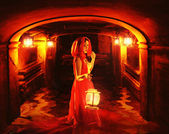 Romantic lady in red holding a lantern in a dark dungeon — Stock Photo