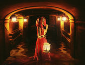 Romantic lady holding a lantern in a dark dungeon — Stock Photo