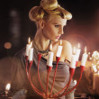 Serious blonde attractive woman keping candlestick - Stok fotoğraf