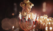 Serious blonde attractive woman keping candlestick — Stock Photo