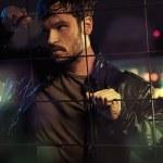 hombre atractivo detrás de vallas de metal — Foto de Stock