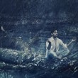 Art photo of handsome man meditating in the rain - Foto Stock