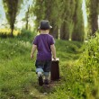 Little child carrying a suitcase — Stock Photo