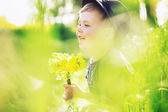 Smiling boy holding yellow flowers — Stock Photo