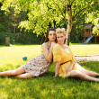 Stock Photo: Two attractive women resting on the flower meadow