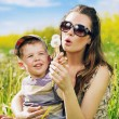 Pretty young mother playing dandelions with son — Stockfoto