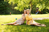 Two attractive women resting on the flower meadow — Stock Photo