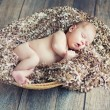 Stock Photo: Newborn baby sleeping in wicker basket