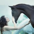 Sensual woman stroking a horse — Stock Photo #27754681