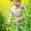 Smiling kid running among the canola flowers — Stock Photo