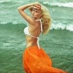 Beautiful blonde girl walking near the sea — Stock Photo