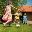 Happy family playing football in the garden — Stock Photo