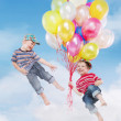 Smiling boys flying with balloons — Stock Photo
