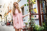 Tall and pretty young model walking in old town — Stock Photo