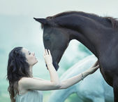 Sensual woman stroking a horse — Stockfoto