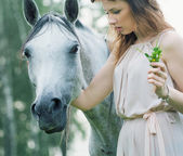 Young woman stroking spotted horse — Stockfoto