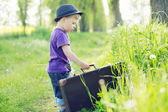 Photo of small kid trying to escape with suitcase — Stock Photo