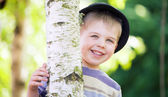 Cheerful boy hiding himself in the garden — Stock Photo
