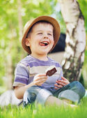 Satisfied little boy consuming an ice cream — Stock Photo