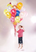 Cute small kid hovering by the ballons — Stock Photo