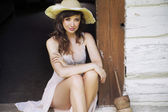 Beautiful brunette woman with straw hat — Stock Photo