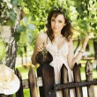 Sexy brunette lady leaning on the wooden fence — ストック写真