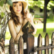 Happy woman leaning on the wooden fence — Stok fotoğraf