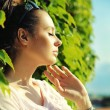 Attractive young woman leaning on plant fence — Stock Photo #29754385