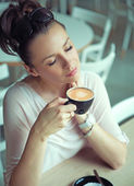 Dreaming brunette lady with cup of coffee — Stock Photo