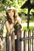 Mulher feliz, apoiando-se na cerca de madeira — Fotografia Stock