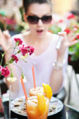 Surprised brunette lady staring at glasses of juice — Stock Photo