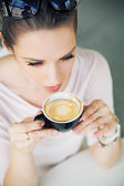 Attractive brunette lady taking a gulp of coffee — Stock Photo