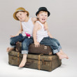 Two small brothers sitting on the suitcases — Stock Photo #31784431
