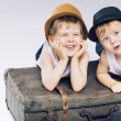 Two cute brothers lying on luggages — Stock Photo
