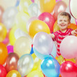 Laughing boy playing among the baloons — Stockfoto