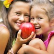 Two sisters sharing a big red apple — Stock Photo