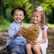 Two laughing kids holding wicker heart — Stock Photo