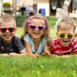 Happy laughing kids lying on the grass — Stock Photo